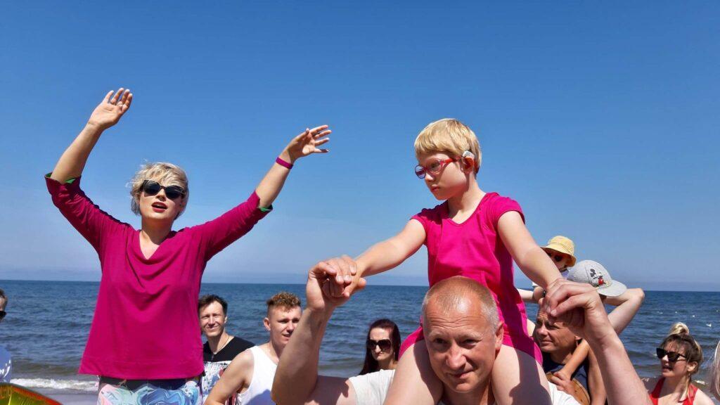 Grupa rodziców i dzieci spaceruje po słonecznej plaży nad morzem.