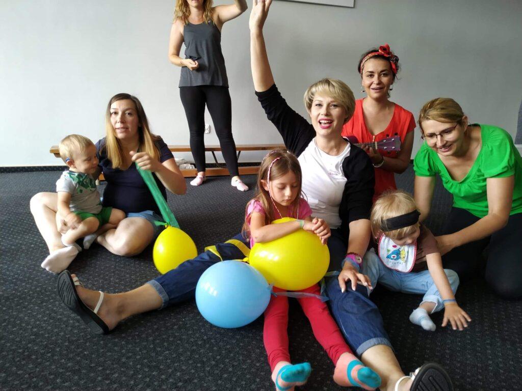 Rodzice i dzieci z kolorowymi balonami.