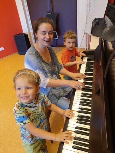 Niesłyszące dzieci razem z instruktorką grają na pianinie w Fundacji Echo