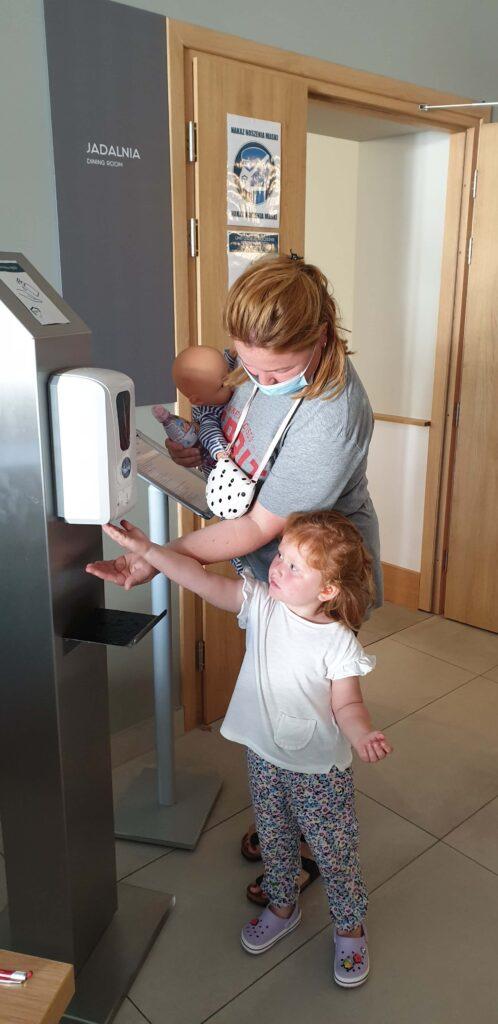 Rodzic i dziecko pobierają płyn dezynfekujący do rąk z automatycznego dozownika.