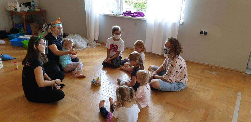 Grupka niesłyszących maluchów podczas zajęć z terapeutami.
