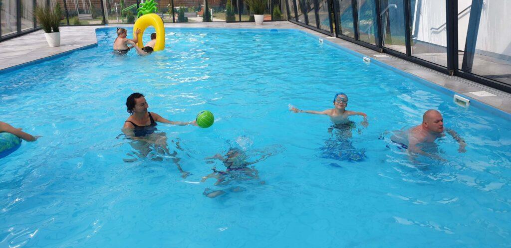 Rodzice i dzieci pływają w basenie