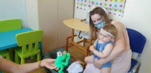 Siedząca mama z niesłyszącym maluchem na kolanach patrzą na pluszową zieloną żabkę.