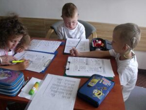 Dzieci z implantami ślimakowymi podczas turnusu rehabilitacyjnego rozwiązują zadania na papierze.