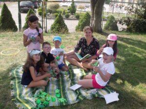 Dzieci bawią się na kocu w cieniu pod drzewem.
