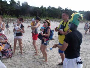 Miedosłyszące maluchy z rodzicami na piaszczystej plaży w towarzystwie króla Juliana.