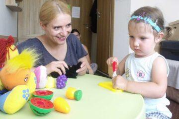 Dziewczynka z implantem ślimakowym siedzi przy stole i przygląda się kolorowym zabawkom.