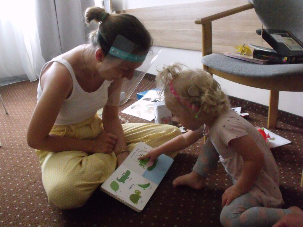 Niedosłyszące dziecko ogląda książkę
