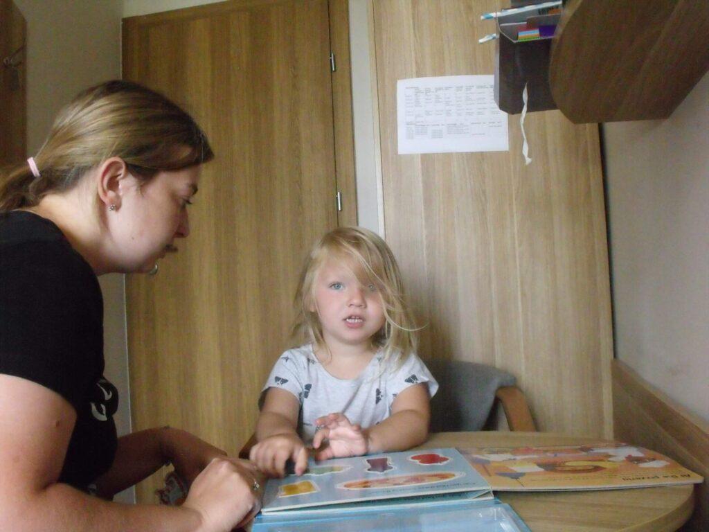 Niedosłysząca dziewczynka przegląda kolorową książkę.