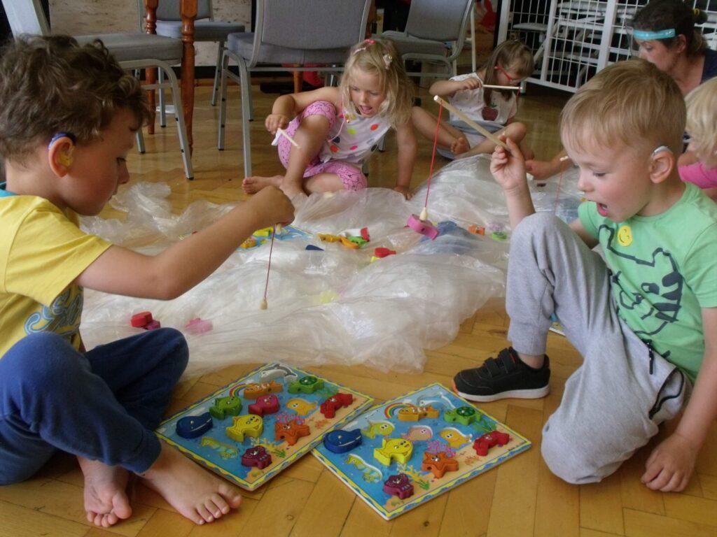 Niedosłyszące dzieci łowią kolorowe rybki na mini wędki.