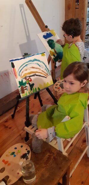 Podopieczni Fundacji Echo malują pędzlami piękne obrazy, używając kolorowych farb.
