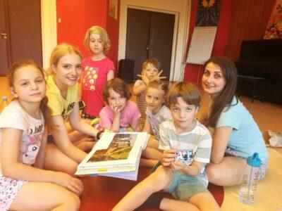 Grupa niesłyszących dzieci wraz z terapeutą przeglądają album ze zdjęciami.