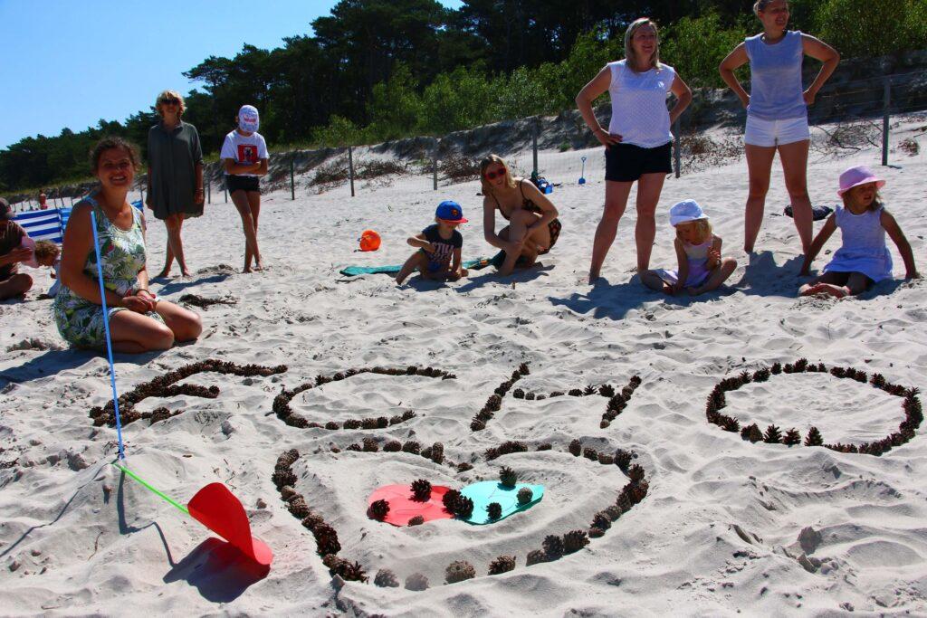 """Dzieci i rodzice ułożyli na piasku napis z szyszek ,,ECHO"""" oraz serduszko."""