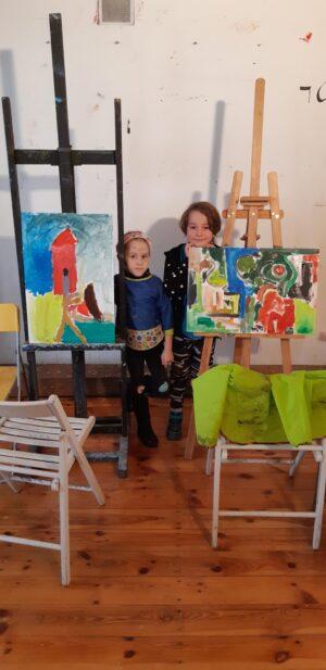Niedosłyszące dzieci stoją pomiędzy pięknymi kolorowymi obrazami.