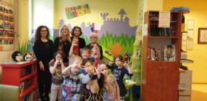 Grupa 6-7 letnich dzieci oraz specjalistów na tle kolorowego kącika zabaw w Fundacji -ECHO-.