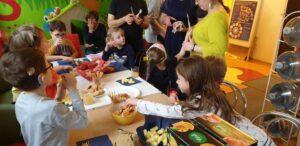 W przerwie podczas turnusu stacjonarnego w Fundacji -ECHO- niedosłyszące dzieci siedzą przy stole i zajadają się słodkościami.