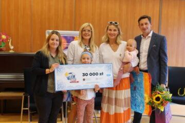 Na zdjęciu są: Prezes Fundacji Echo, zwyciężcy teleturnieju Joanna Moro i Mirosław Szpilewski oraz podopieczni Fundacji z wielkim czekiem na 30 tys. zł.